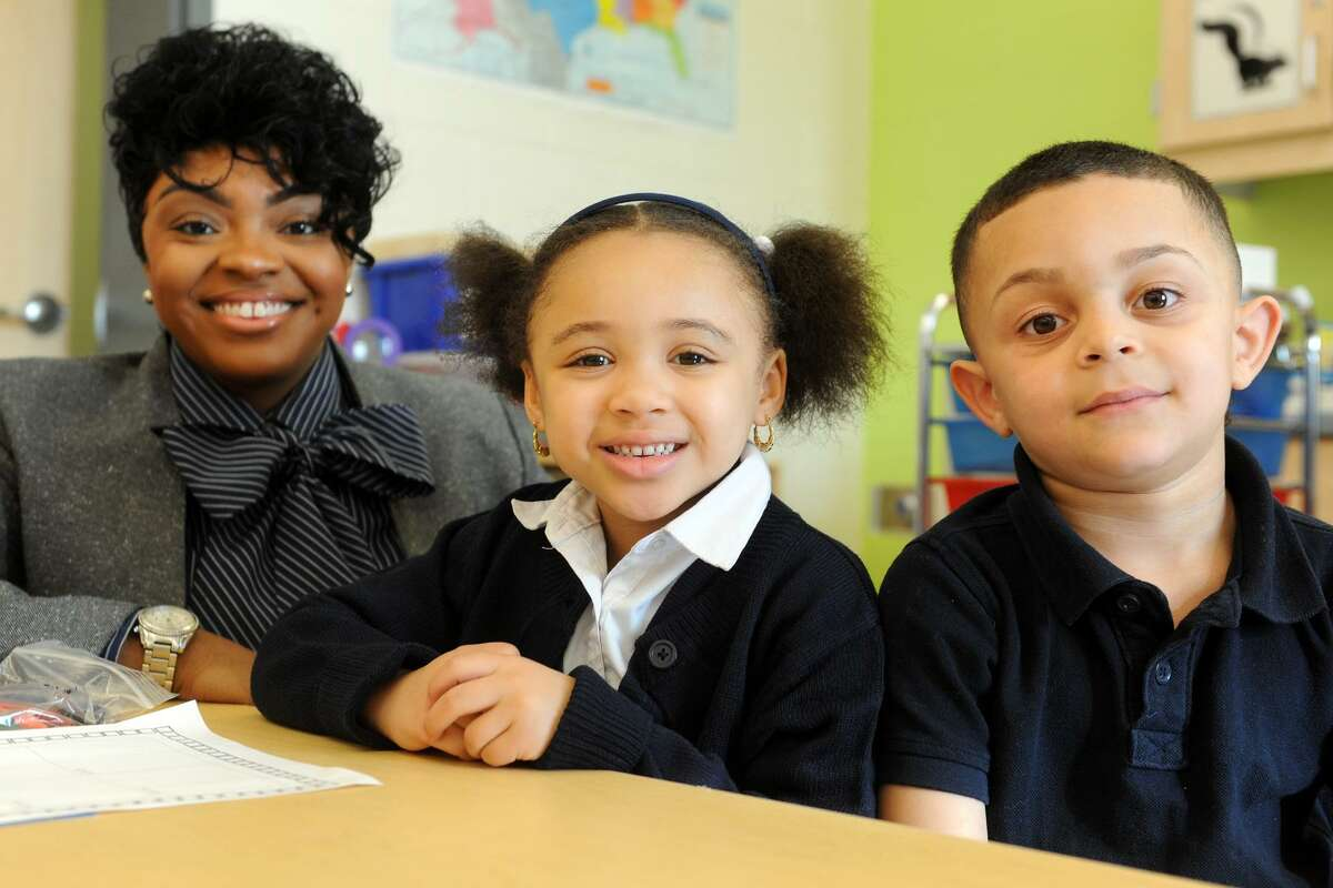 Bennyta Thompson, left, sits with kindergartners J?'anni Reyes and Esteban Sotomayer on the first day of classes at the new Geraldine Claytor Magnet Academy, in Bridgeport, Conn. Jan. 4, 2017. Thompson is daughter of the late Prophetess Geraldine Clayton, for whom the school is named.