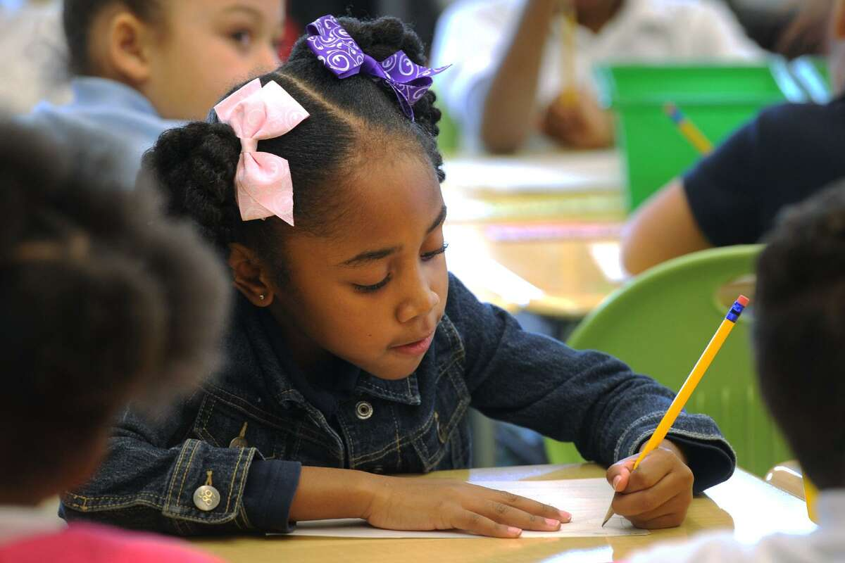 First grader Brylee Kelly works on an assignment on the first day of classes at the new Geraldine Claytor Magnet Academy, in Bridgeport, Conn. Jan. 4, 2017.