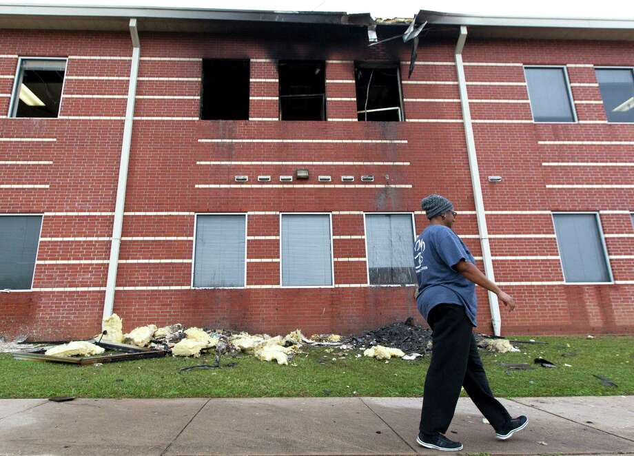 A woman walks past a damaged section of Bear Branch Junior High School after a fire broke out around 12:20 a.m. Wednesday, Dec. 28, 2016, in Magnolia. Photo: Jason Fochtman, Staff Photographer / Houston Chronicle