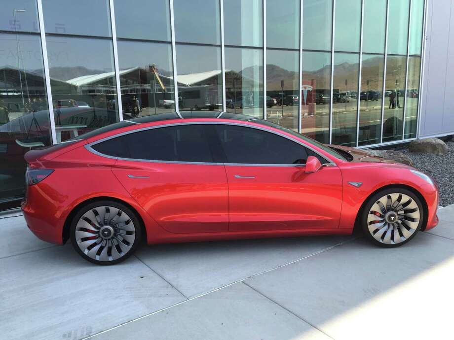 A prototype of the $35,000 Tesla Motors Model 3 sits outside the company's Gigafactory in Nevada. The first battery cells rolled off production lines at the Gigafactory on Wednesday. The battery cells will power the company's energy storage products and, before long, the Model 3 electric car. Photo: David R. Baker /San Francisco Chronicle