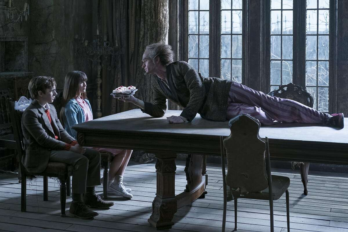 Neil Patrick Harris gives the character of Count Olaf his sinister best as he illustrates as he viciously crawls down tne table to inform the horrified Baudelaire orphans of his latest scheme in 'A Series of Unfortunate Events' on Netflix.