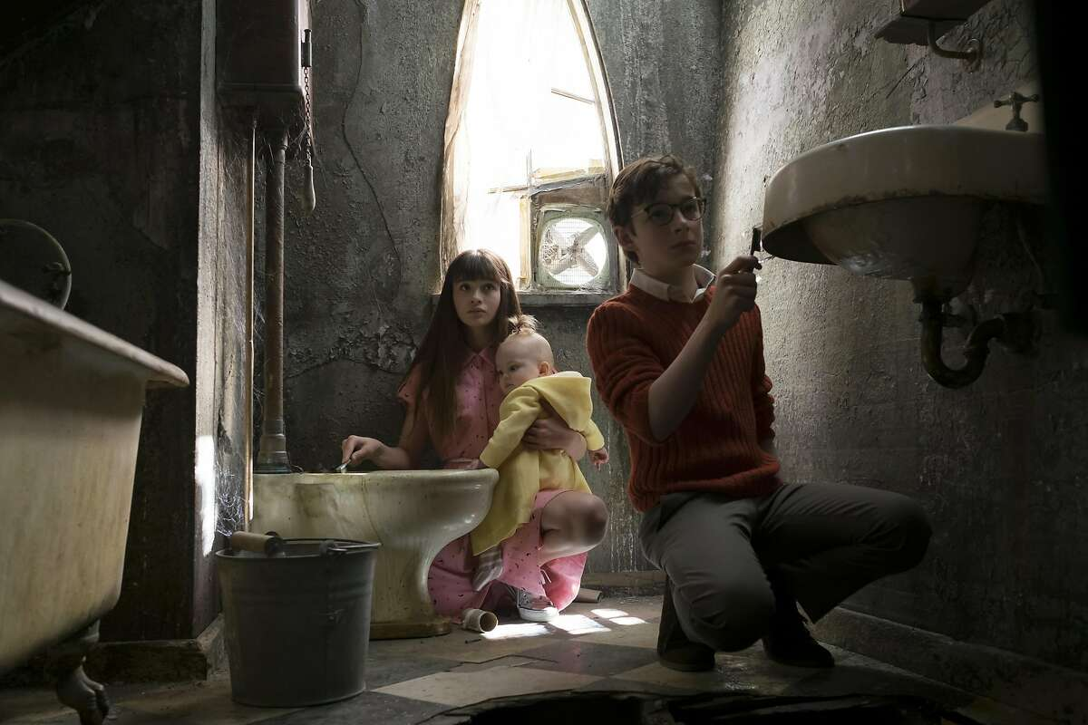 The Baudelaire orphans (Malina Weissman as Violet, Presley Smith as baby Sunny and Louis Hynes as Klaus) are forced to clean Count Olaf's disgusting, rat-infested bathroom with toothbrushes in 'A Series of Unfortunate Events' on Netflix.