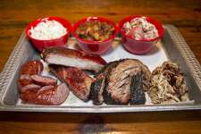 A barbecue tray of sausage, pork ribs, brisket, pulled pork and sides of cole slaw, beans, and potato salad at The Granary.