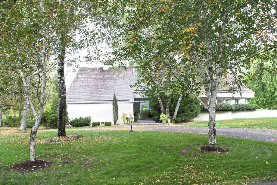 The contemporary house at 12 Hedley Farms Road sits at the end of a private cul-de-sac in a secluded setting along Ardel Pond near Long Island Sound.