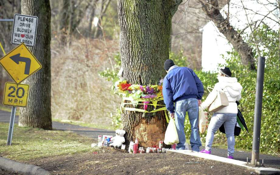 A couple takes a moment to view a makeshift memorial on Jan. 4, 2016 at the site of a New Year's Day crash at Stillwater Avenue and Progress Drive in Stamford that killed a city teenager. Photo: Matthew Brown / Hearst Connecticut Media / Stamford Advocate
