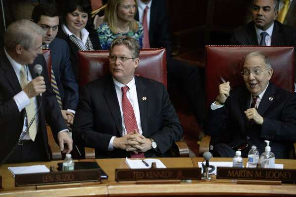 State Sen. Len Suzio, R- Meriden, left, talks to Senate President Pro Tempore Martin M. Looney, D-New Haven, right, as Sen. Ted Kennedy Jr., D-Branford, center, looks on, during opening session at the state Capitol, Wednesday, Jan. 4, 2017, in Hartford, Conn.