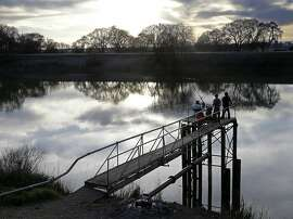 FILE- In this Feb. 23, 2016 file photo, people try to catch fish along the Sacramento River in the San Joaquin-Sacramento River Delta, near Courtland, Calif. California has released a key environmental report supporting Gov. Jerry Brown's plans for two giant north-south water tunnels. Brown's administration environmental-impact report Thursday, Dec. 22, 2016, for the project clears another regulatory hurdle for the proposed tunnels. (AP Photo/Rich Pedroncelli, File)