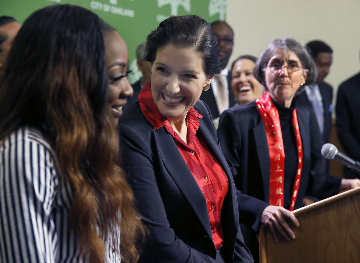Oakland Mayor Libby Schaaf chats with Mya Whitaker, with the Bay Area Urban Debate League, after naming Anne Kirkpatrick (right) the new chief of police at a news conference in Oakland, Calif. on Wednesday, Jan. 4, 2017.