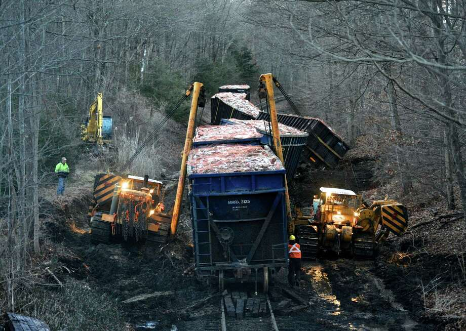 Workers from Advanced Construction, in New Milford, use two Caterpillar D9 Sidewinders to lift derailed freight cars in Brookfield, Conn, on Wednesday, January 4, 2016. The CAT D9's are used to lift and place the rail cars back on the tracks. Photo: H John Voorhees III, Hearst Connecticut Media / The News-Times
