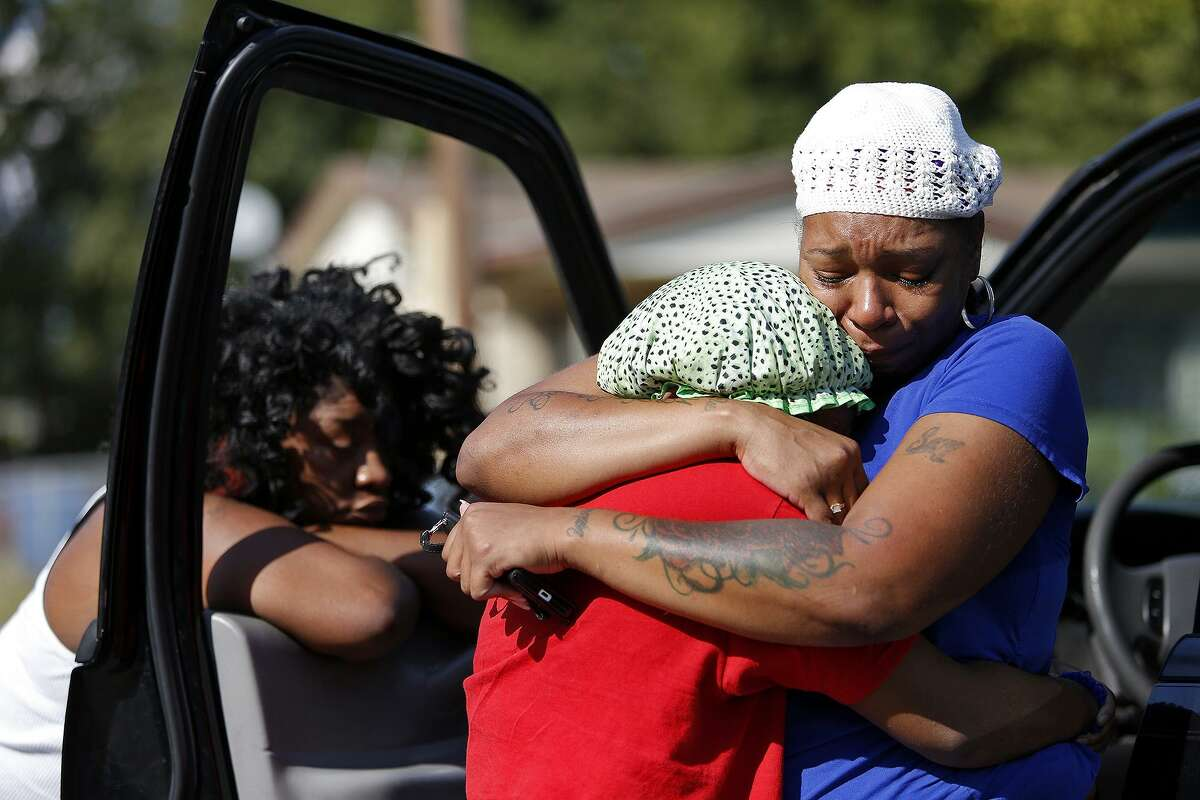 Jillian Peterson embraces Shavonne Ferguson, 15, at the placed where a young man was shot and killed and another was injured in San Antonio on Sept. 26, 2015. The women believed the victim to be their friend, Tru Trusty, 16.