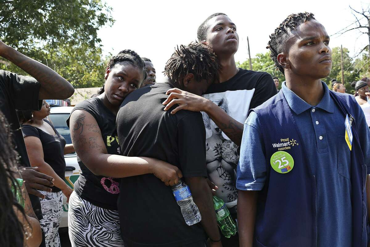 Friends and family of Tru Trusty, 16, watch as detectives and the medical examiner work on the case of a young man who was shot and killed Sept. 26, 2015.
