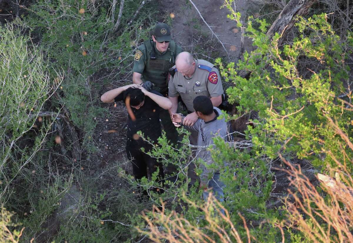 MCALLEN, TX - OCTOBER 18: A Texas state trooper and a U.S. Border Patrol agent detain undocumented immigrants on October 18, 2016 near McAllen, Texas. Immigration and border security have become major issues in the American Presidential campaign. (Photo by John Moore/Getty Images) *** BESTPIX ***