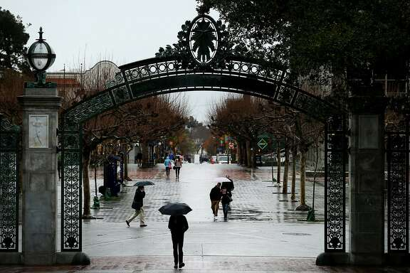 People make their way by Sather Gate during the rain at UC Berkeley on Wednesday, Jan. 4, 2017 in Berkeley, Calif. Tuition at the University of California is expected to grow for the first time since 2011 under a proposal the UC regents will consider this month.