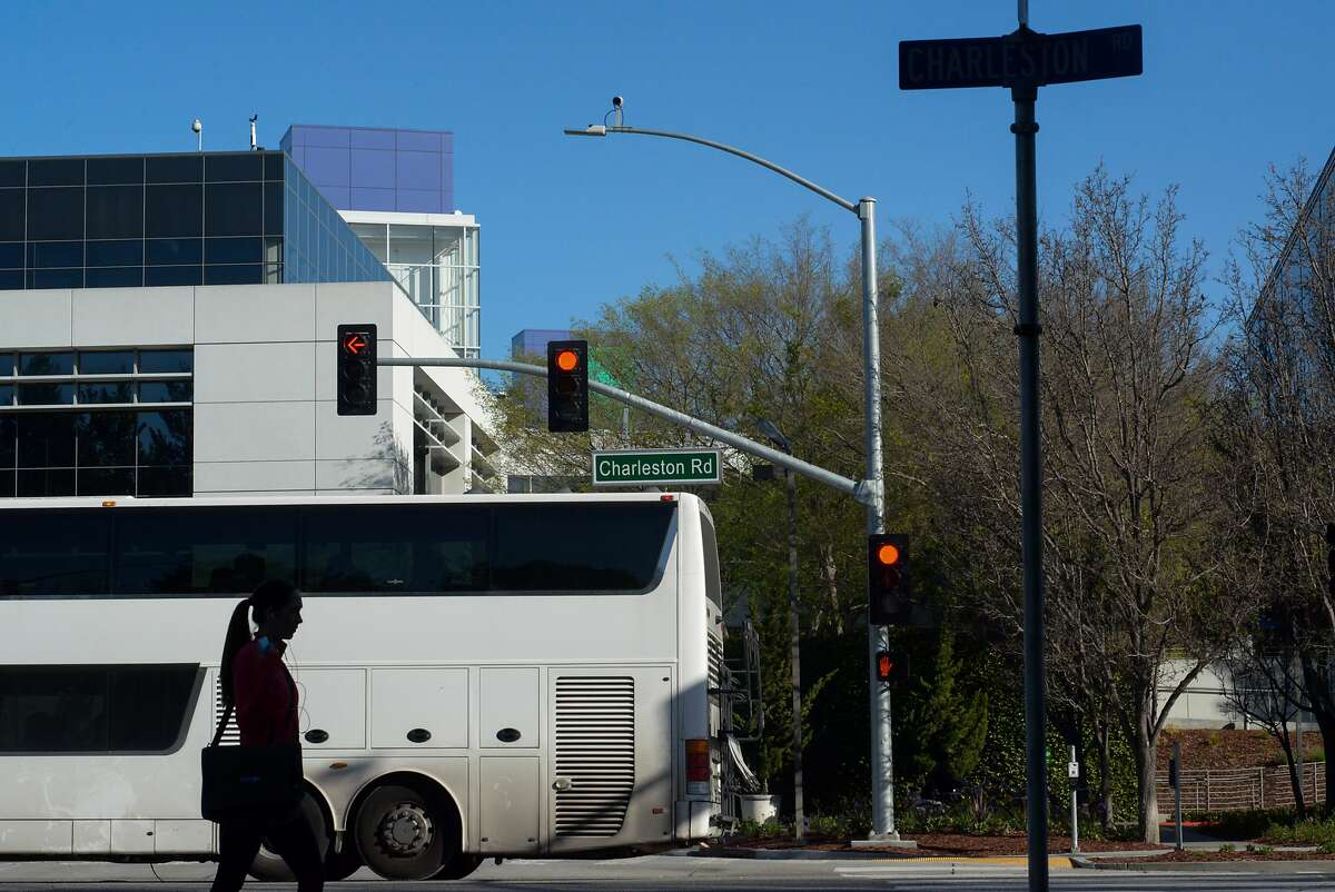 A woman and a Google Bus cross paths on Charleston Rd. at Google's campus in Mountain View, Calif. on Friday, March 6, 2015. Google has proposed developments around their campus to the city of Mountain View.