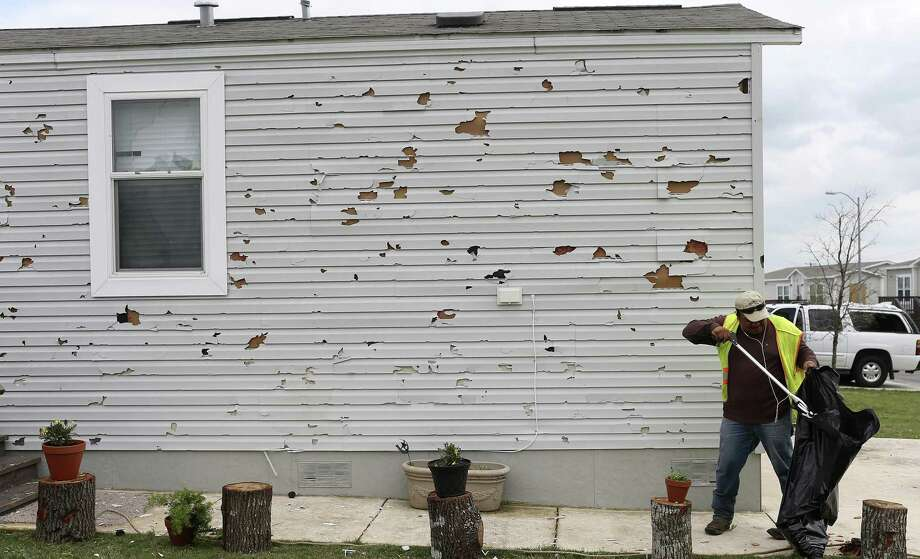 Roberto Torres picks up debris at the Woodlake Estates on the cityís northeast side on April 13, 2016, after a severe hailstorm hit the area. So-called Blue Tarp bills in the Legislature will weaken your ability to collect from your insurance company? Photo: JERRY LARA /San Antonio Express-News / © 2016 San Antonio Express-News