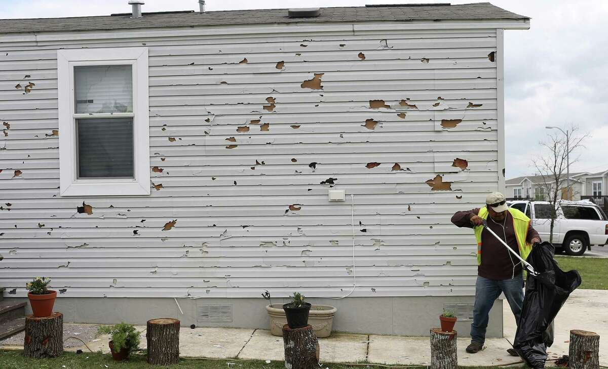 A residentpicks up debris at the Woodlake Estates following a severe hailstorm in April. HB1774 would protect consumers from storm-chasing lawyers exploiting natural disasters.