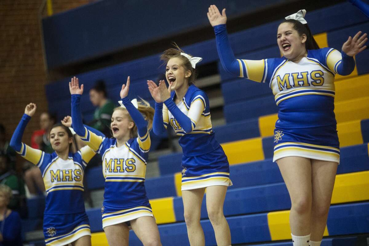 Midland Varsity Cheer claps while entering the mat to compete in the Sixth Annual Chemic Cheer Invitational on Wednesday at Midland High School. Midland hosted Dow, Meridian, Saginaw Heritage, Vassar, Jefferson Middle School and Northeast Middle School at the competition.