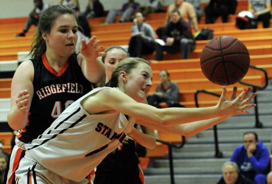 Stamford Megan Landsiedel reaches for the savel under pressure from Ridgefield Elizabeth Middlebrook in a FCIAC varsity girls basketball game at Stamford High School on Jan. 4, 2016. Ridgefield defeated Stamford 43-39. Photo: Matthew Brown / Hearst Connecticut Media / Stamford Advocate