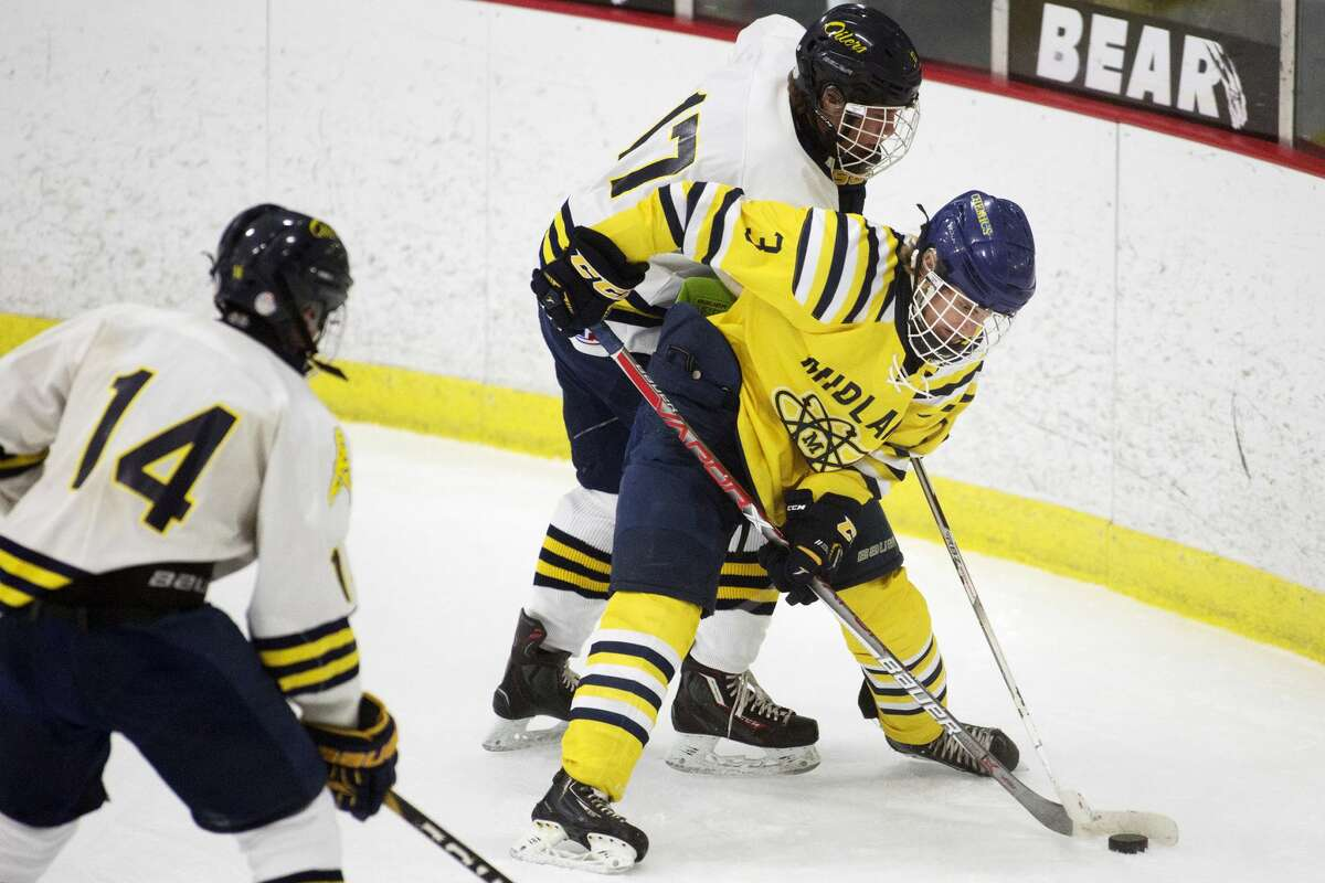Midland's Dylan Sirrine fights for control of the puck while being defended by with Mt. Pleasant's Cole Smallwood in a game at Midland Civic Arena on Wednesday.