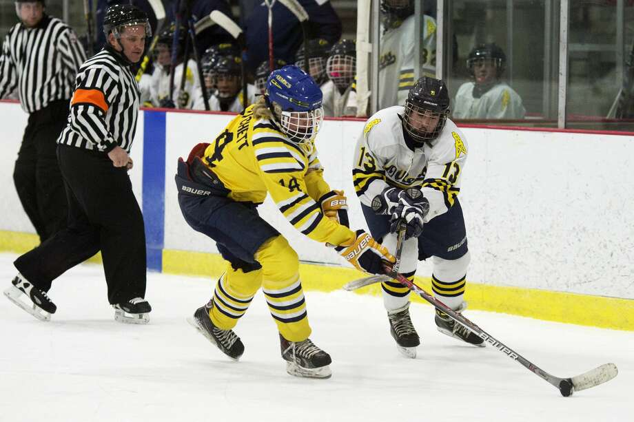 Midland's Tommy Pritchett fights for control of the puck with Mt. Pleasant's Eli Kea in a game at Midland Civic Arena on Wednesday. Photo: Theophil Syslo For The Daily News