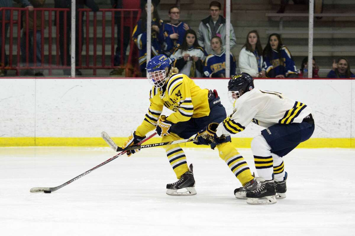 Midland's Tommy Pritchett attempts to shoot the puck while being defended by Mt. Pleasant's Kaleb Ramon in a game at Midland Civic Arena on Wednesday.