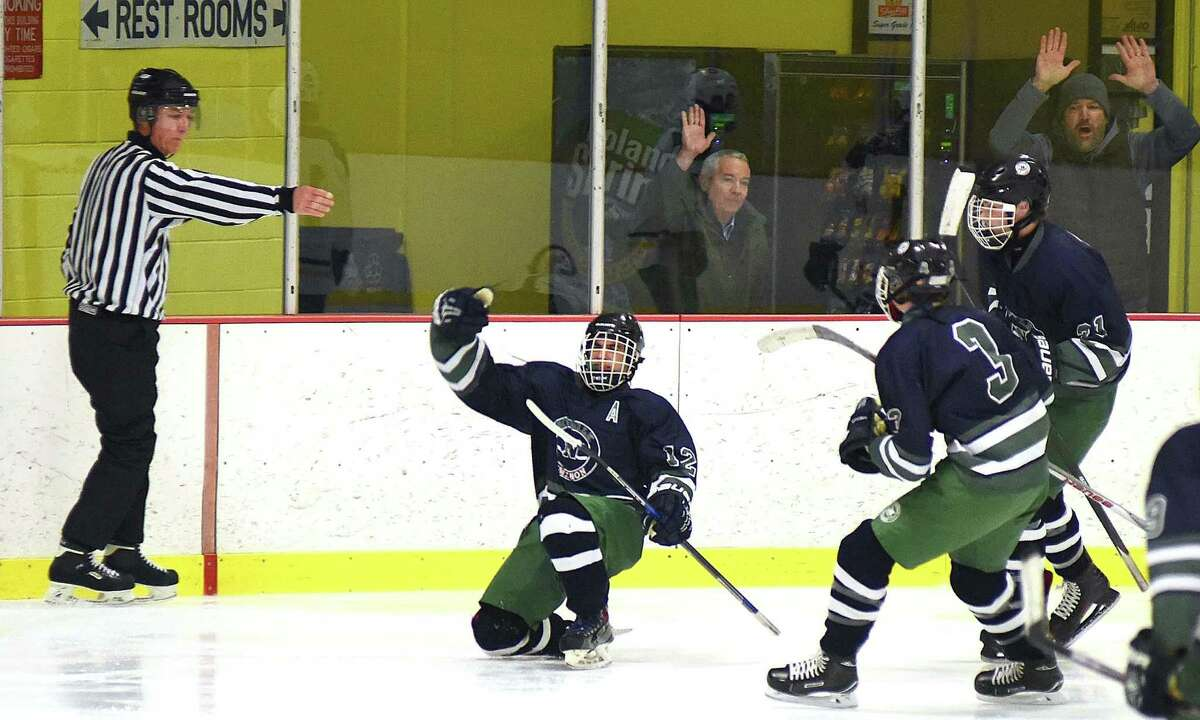 As the official signals a goal with 2:15 left in the game, Norwalk-McMahon's Dylan Persons, center, celebrates his tally that gave his team a 4-3 win over Trinity Catholic on Wednesday night at Terry Conners Rink in Stamford.