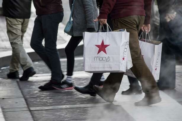 A shopper carries Macy's Inc. shopping bags in San Francisco, California, U.S., on Monday, Dec. 26, 2016. The Bloomberg Consumer Comfort Index, a survey which measures attitudes about the economy, is scheduled to be released on December 29. Photographer: David Paul Morris/Bloomberg