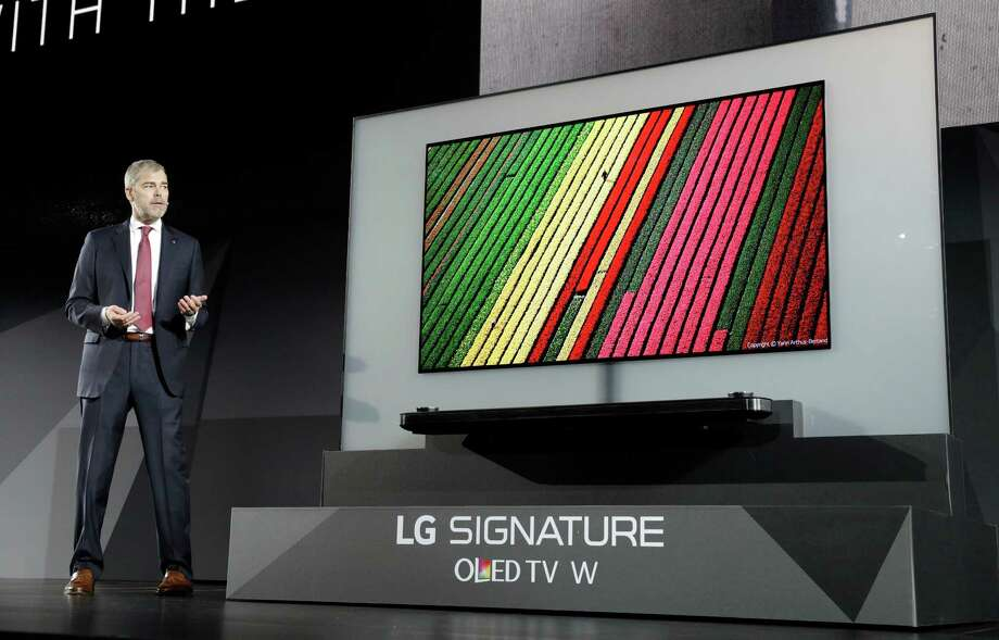 David VanderWaal, vice president of marketing for LG Electronics USA, unveils the LG Signature OLED TV W during an LG news conference before CES International, Wednesday, Jan. 4, 2017, in Las Vegas. (AP Photo/John Locher) ORG XMIT: NVJL102 Photo: John Locher / Copyright 2017 The Associated Press. All rights reserved.