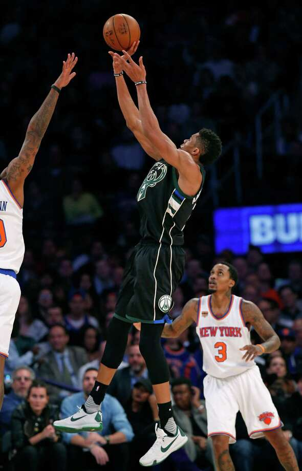 Milwaukee Bucks' forward Giannis Antetokounmpo (34) shoots beyond a New York Knicks' defender with Knicks' guard Brandon Jennings (3) looking on in the second half of an NBA basketball game at Madison Square Garden in New York, Wednesday, Jan. 4, 2017. The Bucks defeated the Knicks 105-104 on Antetokounmpo's buzzer beater. (AP Photo/Kathy Willens) ORG XMIT: MSG113 Photo: Kathy Willens / Copyright 2017 The Associated Press. All rights reserved.