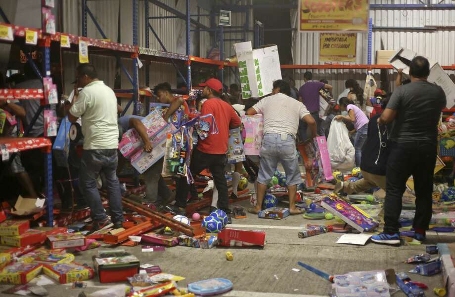 A group of people grabs toys as a store is ransacked by a crowd in the port of Veracruz, Mexico, Wednesday Jan. 4, 2017. Protests over a sharp gasoline price hike erupted into looting of gas stations and stores in various parts of Mexico on Wednesday, with dozens of businesses reportedly sacked. In the Gulf coast state of Veracruz, store guards were overrun by crowds who carried off clothing, toys, food, washing machines, televisions, DVD players and refrigerators.(AP Photo/Ilse Huesca) Photo: Ilse Huesca/AP
