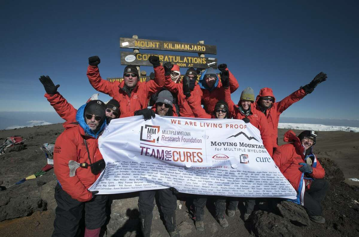 The 2016 Mount Kilimanjaro team at the summit, holding a banner with more than 100 names of multiple myeloma patients written on it.