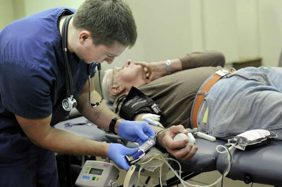 Chris Banziruk, 26, of Oxford, Conn., a phlebotomist with the American Red Cross draws blood from Harry Doyle, 76, of Danbury Saturday, January 24, 2015. The American Red Croos held a blood drive Saturday on Delay Street in Danbury. Doyle, a regular blood donor,  didn't let Saturday's snow storm keep him from his appointment. Photo: Carol Kaliff / Carol Kaliff / The News-Times