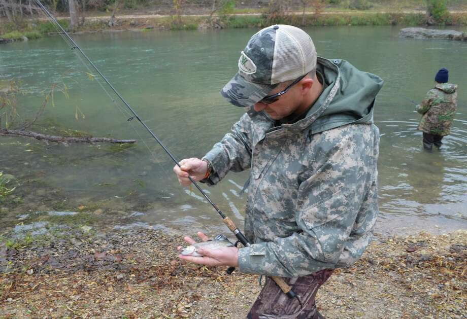Taking one last look before returning this rainbow trout to the Guadalupe River, Matt Lowell is a regular angler taking advantage of the fishing opportunities at Camp Huaco Springs. Photo: Ralph Winingham / For The Express-News /