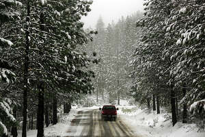 A snow-covered Elk Mountain Road in the Mendocino National Forest above Upper Lake, Calif., greets a driver during a low-elevation snowfall, Tuesday Jan. 3, 2017. (Kent Porter/The Press Democrat via AP)