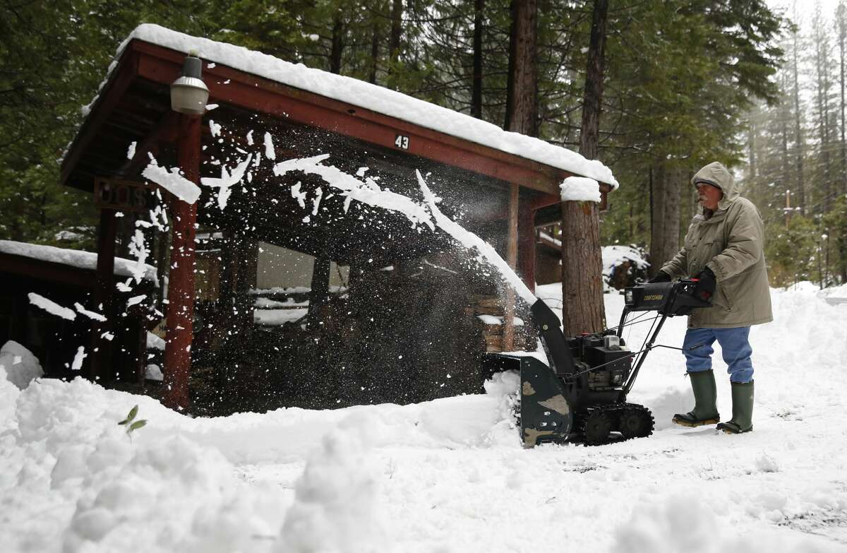 Joe Johnson clears the snow from a neighbor's driveway near Kyburz, Calif., Tuesday, Jan. 3, 2017. The California Department of Water Resources held the first manual snow survey of the season near Phillips Station near Echo Summit, on Tuesday. The survey showed the snowpack at 53 percent of normal at the site for this time of year.(AP Photo/Rich Pedroncelli)