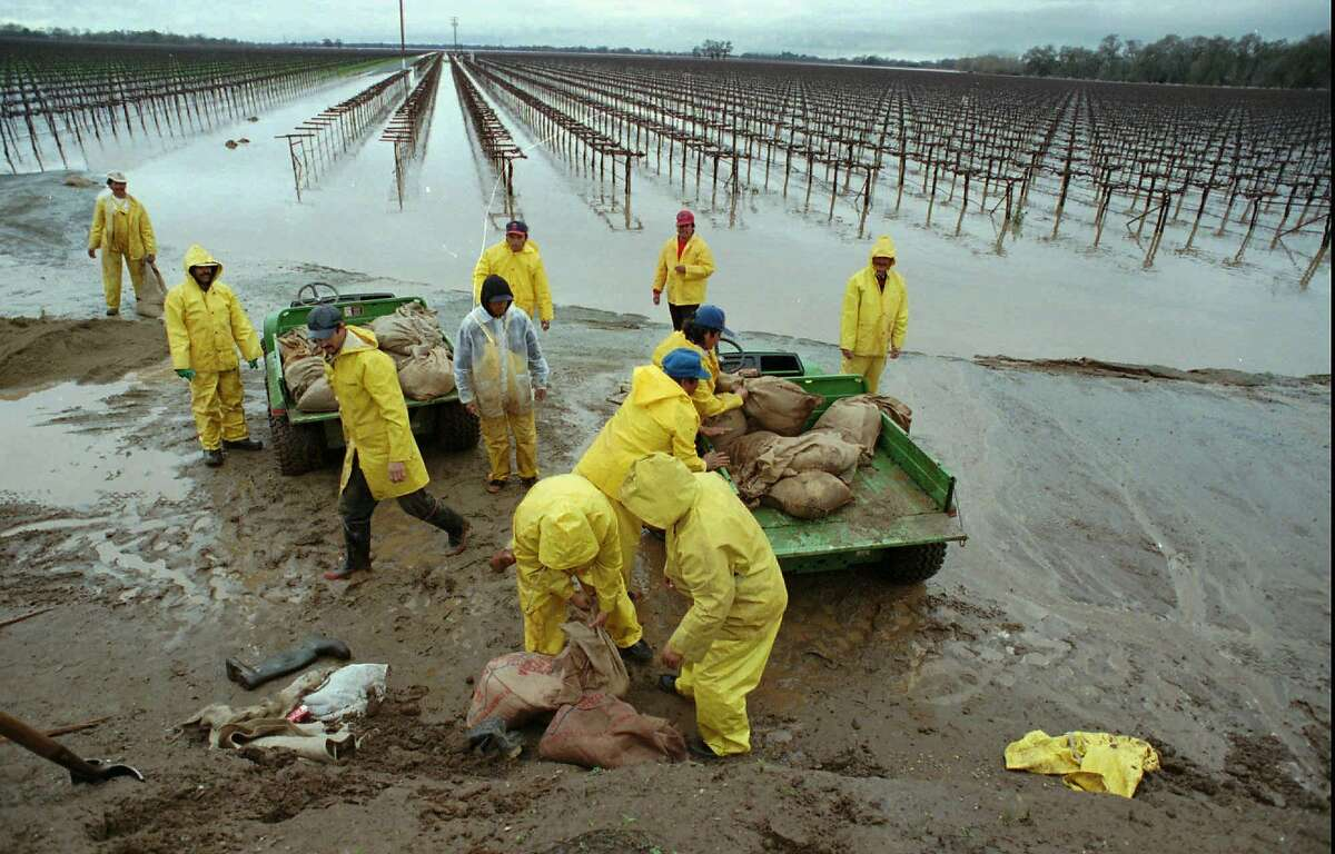 FLOOD3/C/02JAN97/MN/SY - Farm workers rush to sandbag around a road near Wilton, Calif., were the Consumnes River crested over its banks into a nearby grape field, Thursday, Jan. 2, 1997. photo/Steve Yeater)