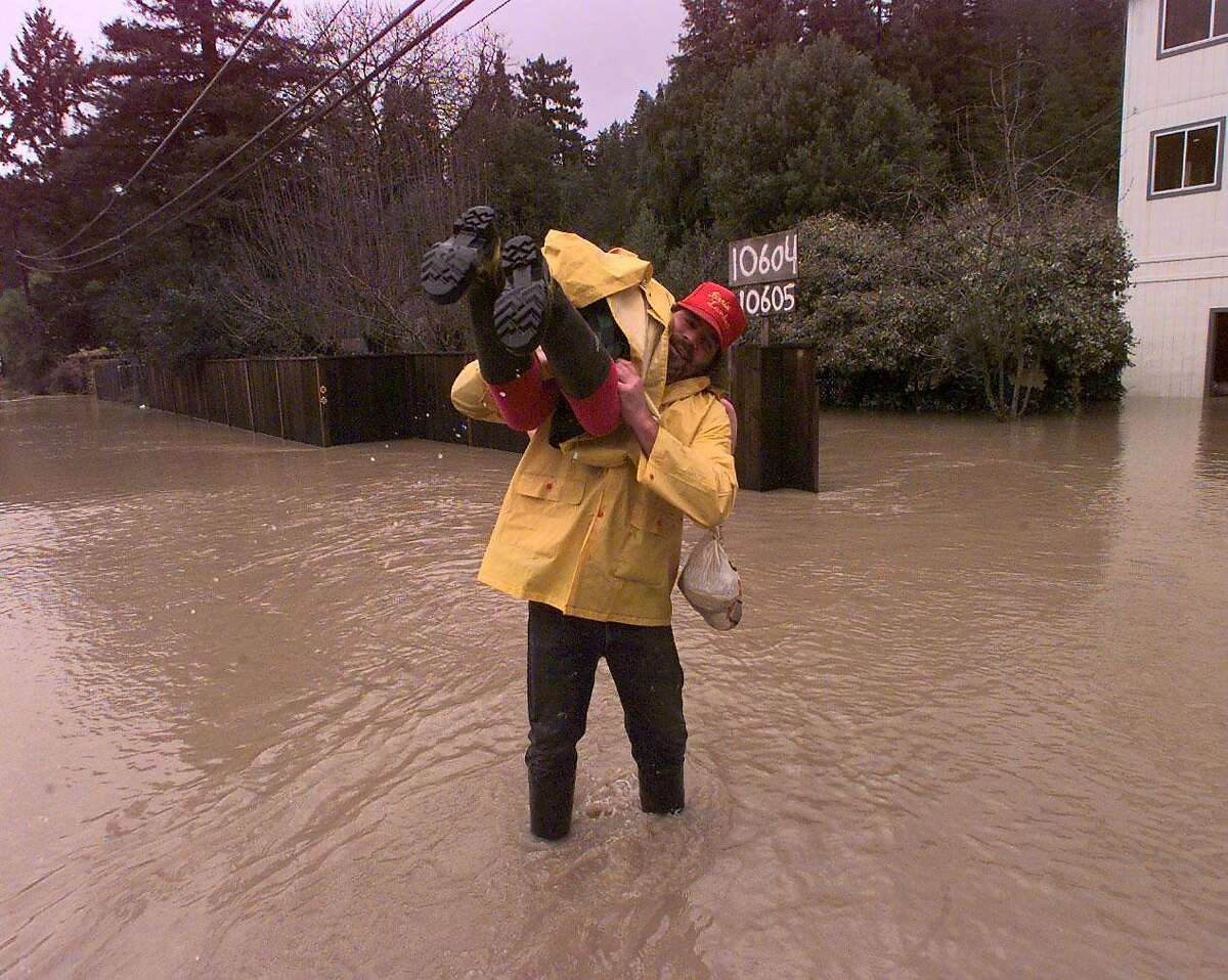 """FLOOD-LIFT 2/C/02JAN97/CD/CS - Irv Levikow (cq) carries his wife Dennise through deep water to their River Road home near the Hacienda bridge along the Russian River. Levikow has already carried his daughter Elise, 5, through the water. They had left their home for companionship at a local pub because """"We needed human beings,"""" said Silkey. SAN FRANCISCO CHRONICLE PHOTO BY CHRIS STEWART"""