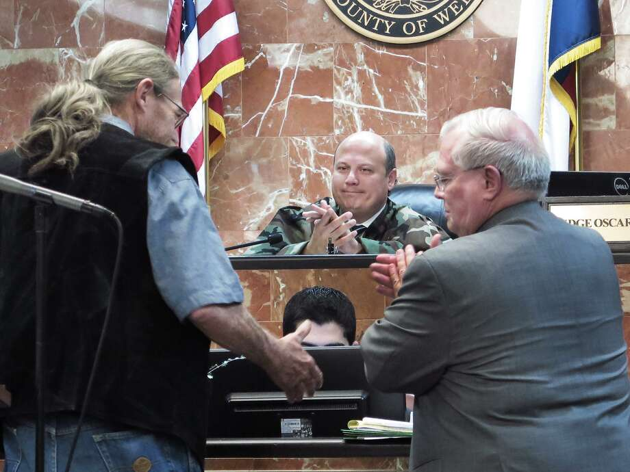 406th District Judge Oscar J. Hale Jr., center, watches as one of five graduates of the Eight 406th and 341st District Courts Veterans Treatment Program shakes hands with a representative of the Webb County District Attorney's office Wednesday afternoon after being recognized as a graduate of the 12-18 month program. Photo: Cuate Santos / Laredo Morning Times / Laredo Morning Times