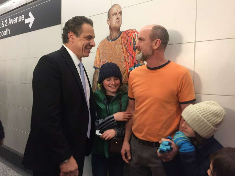 The photo posted on the Twitter account of Gov. Andrew Cuomo (left) with Michael Whitney and his children in front of the Vik Muniz mosaic of Whitney in the Second Avenue subway station in New York City. (Executive Chamber)