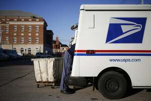 A United States Postal Service (USPS) letter carrier loads mail onto a Grumman Long Life Vehicle (LLV) in Shelbyville, Kentucky, U.S., on Thursday, Dec. 22, 2016. More than 30 million packages handled by the USPS are estimated to be delivered on December 22, which is still a fraction of the 750 million packages this holiday season, a 12 percent increase over last year. Photographer: Luke Sharrett/Bloomberg