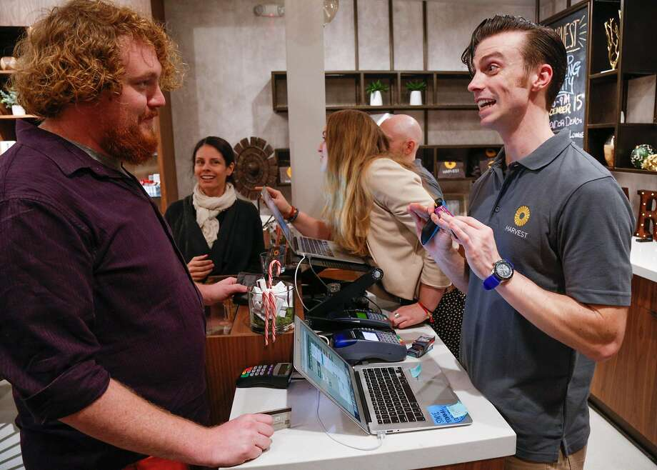 From left, Darryl Van Minnen makes a purchase from James Kleier at Harvest, a new dispensary in the Bernal Heights neighborhood. Harvest celebrated it's grand opening Thursday evening, December 15, 2016 in San Francisco. Brian Feulner, Special to the Chronicle Photo: Brian Feulner, Special To The Chronicle