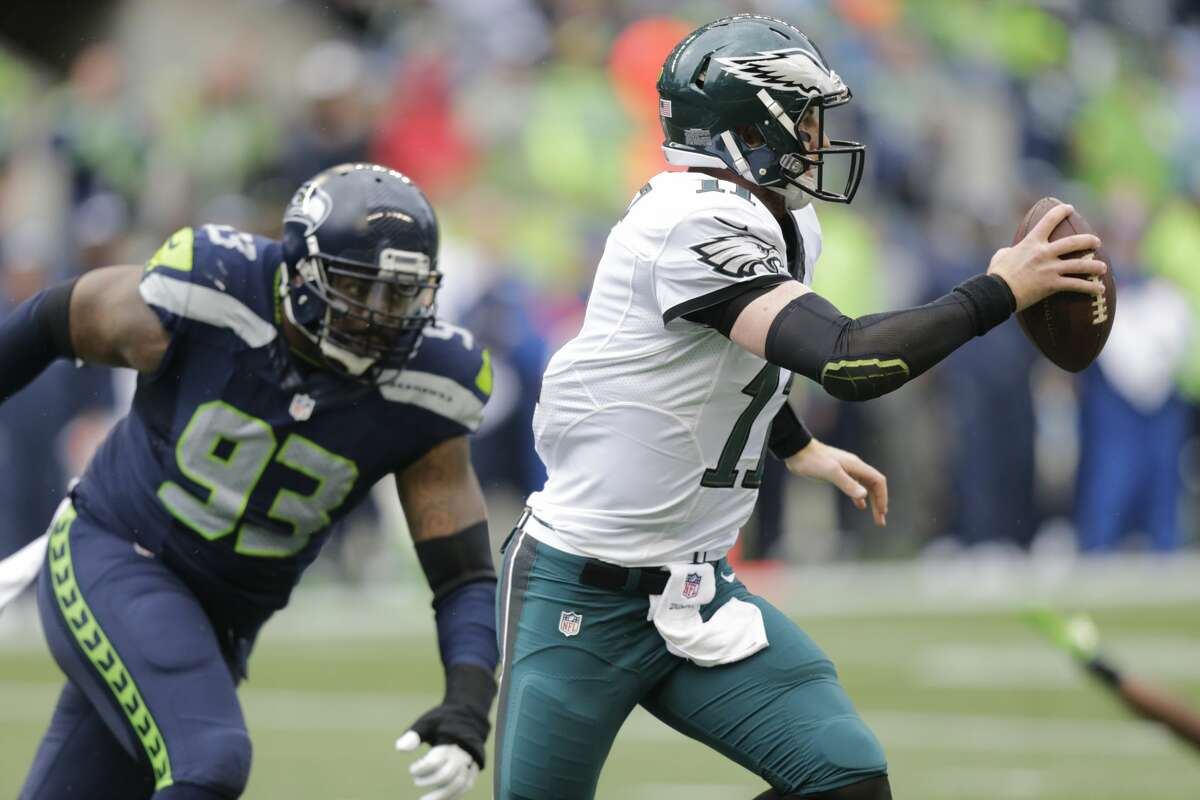Philadelphia Eagles quarterback Carson Wentz, right, scrambles away from Seattle Seahawks defensive tackle Tony McDaniel (93) in the first half of an NFL football game, Sunday, Nov. 20, 2016, in Seattle. (AP Photo/Stephen Brashear)