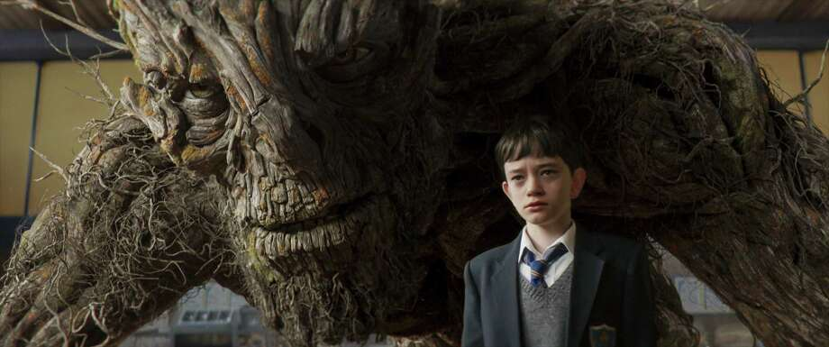 """This image released by Focus Features, Lewis MacDougall appears with The Monster, voiced and performed by Liam Neeson, in a scene from """"A Monster Calls."""" (Focus Features via AP) ORG XMIT: NYET265 / 2016 Focus Features, LLC."""