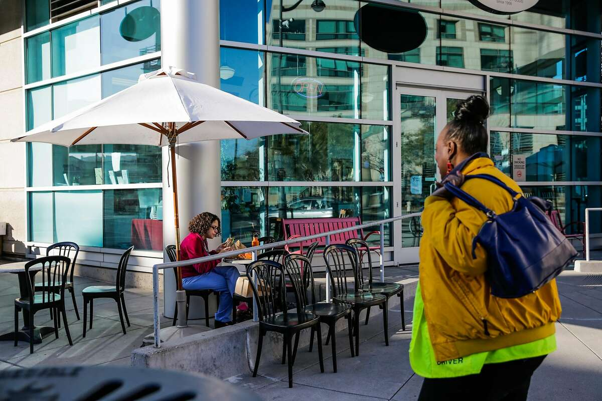 Alisa Amaral (left) eats lunch outside Esposto's Delicatessen on 16th Street, in the Mission Bay neighborhood, in San Francisco, Calif., on Thursday, Dec. 22, 2016.