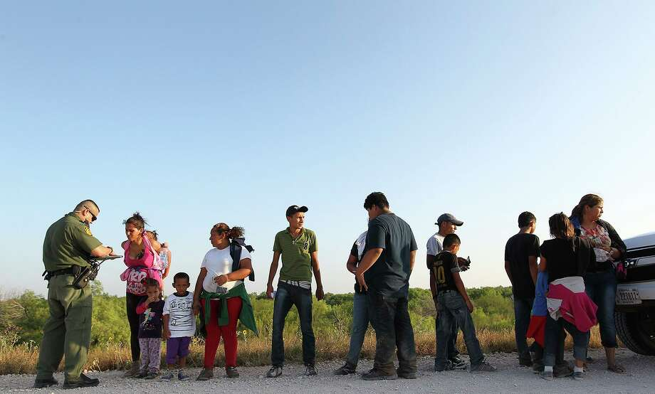 U.S. Border Patrol agents question a group of adult and minor immigrants who walked up to them near Anzalduas Park, southwest of McAllen, Texas, Wednesday, June 11, 2014. To avoid media attention, agents on the scene hustled the immigrants into a nearby transportation van. A wave of Central American adults with children and unaccompanied minors has overwhelmed U.S. Immigration and Customs detention centers. Immigration officials release some of them on their own recognizance after undergoing processing. Photo: Jerry Lara, Staff / ©2014 San Antonio Express-News