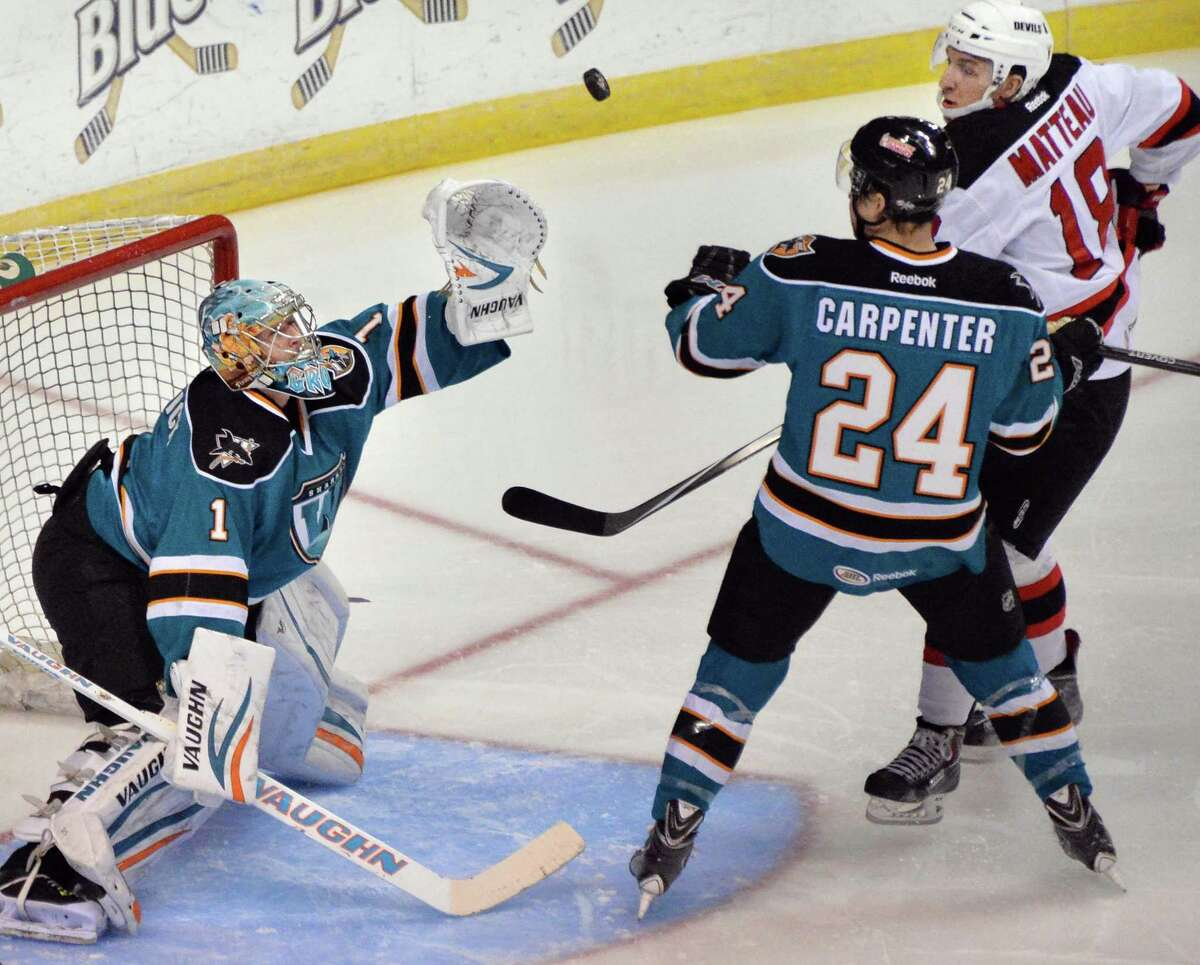 Worcester Sharks goalie and former Union player, Troy Grosenick, left, stops an Albany Devils' shot during Saturday's game at the Times Union Center March 29, 2014, in Albany, NY. (John Carl D'Annibale / Times Union) ORG XMIT: MER2014032919434689