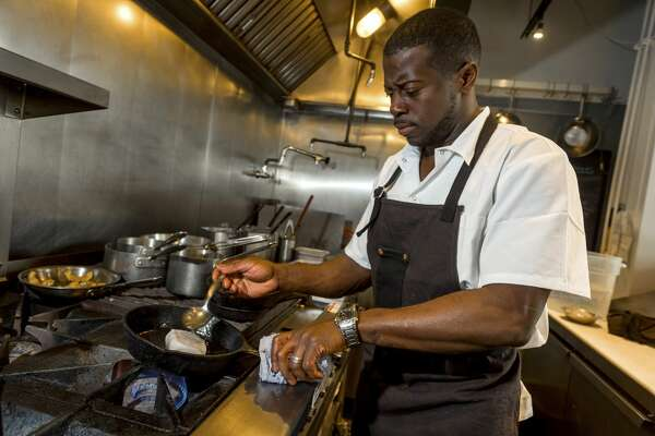 """Edouardo Jordan prepares black cod at Salare, his restaurant in Seattle, Oct. 23, 2015. Jordan, whose dishes merge the cucina povera of Italy, the Southern and Caribbean flavors, is just one of many chefs reinventing African-American cuisine. """"€œWhen I began the process of opening Salare, a little bird kept singing in my head, 'Embrace your heritage,'""""€ he said."""