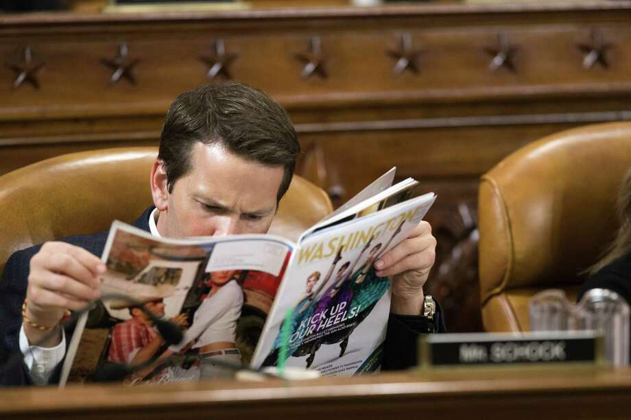 """In this file photo from Friday, April 12, 2013, at a House Ways and Means Committee hearing on President Barack Obama's budget, Rep. Aaron Schock, R-Ill., peruses a magazine as Health and Human Services Secretary Kathleen Sebelius testifies on Medicare spending and other health issues, on Capitol Hill in Washington. The publication Schock is reading is Washington Life magazine, described as """"Washington DC's premier guide to luxury, power, philanthropy & style.""""  Schock's high-flying lifestyle, combined with questions about expenses decorating his office in the style of the TV show """"Downton Abbey,"""" add to awkward perceptions on top of allegations he illegally solicited donations in 2012. The Office of Congressional Ethics said in a 2013 report that there was reason to believe Schock violated House rules by soliciting campaign contributions during a 2012 primary. (AP Photo/J. Scott Applewhite/File) Photo: J. Scott Applewhite, STF / Associated Press / AP"""