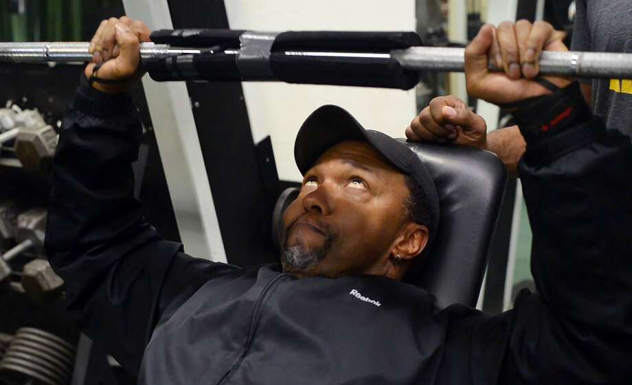 """Gary Shields bench presses a set of weights. Shields has owned the gym for three decades, where he shares his love of body-building and community support. """"If I can help you build a life that's good, right, and true, I'm all for it!"""" Photo: Max Bouvatte, Special To The Chronicle"""