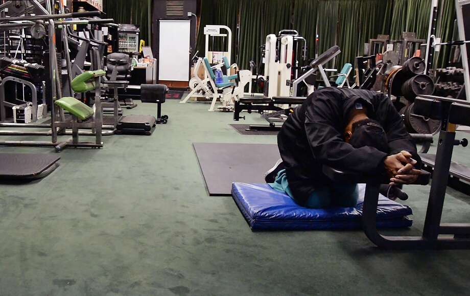 Gary Shields, who has operated his Oakland gym for three decades, prays before he opens up his business. Photo: Max Bouvatte, Specail To The Chronicle